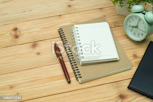 Office supplies or office work essential tools items on wooden desk in workplace, pen with notebook and alarm clock with copy space.