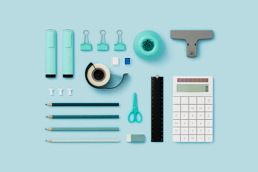 Office supply flat lay on blue background