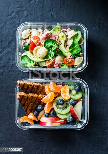 Office sweet and savory food lunch box. Pasta, tuna, spinach, avocado salad and fruit, peanut butter sandwiches lunch box on dark background top view