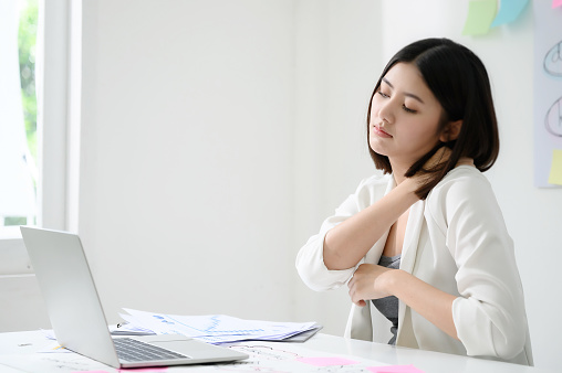 istock Office syndrome concept. Young asian businesswoman feeling pain in neck after working on computer laptop for a long time 1177969662