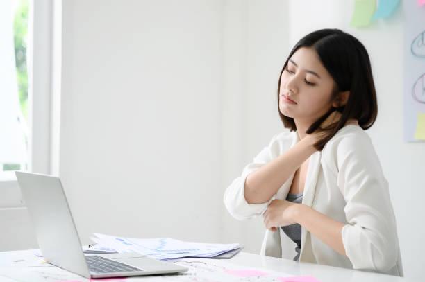 Büro-Syndrom-Konzept. Junge asiatische Geschäftsfrau fühlt Schmerzen im Hals nach der Arbeit auf Computer-Laptop für eine lange Zeit – Foto