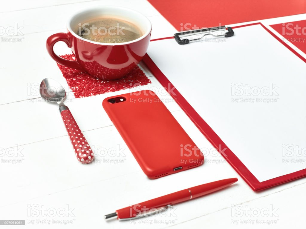 Office table desk with set of colorful supplies, white blank note pad, cup, pen on white background stock photo