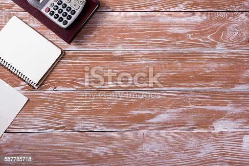 509867718istockphoto Office table desk with supplies, white blank note pad, cup 587785718