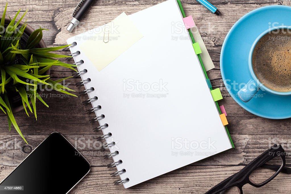 Büro-Tisch mit einer Tasse Kaffee und einem Notizblock – Foto
