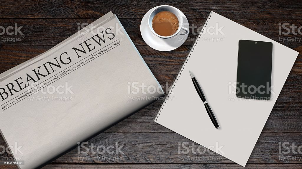 office table with blank newspaper and the headline breaking news stock photo