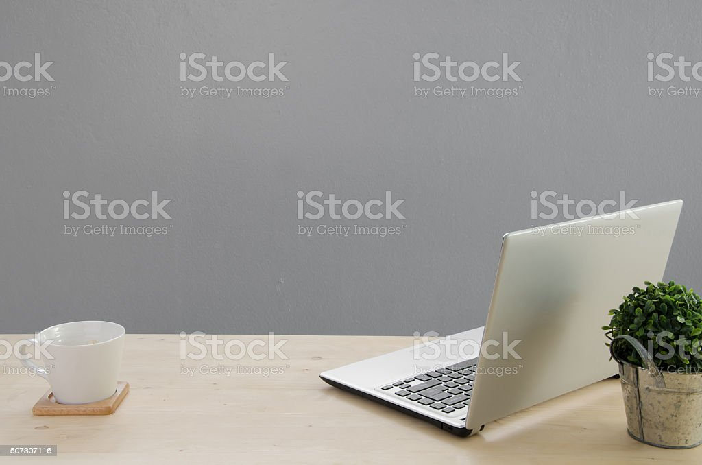 Office table with notebook, green tree on basket. stock photo