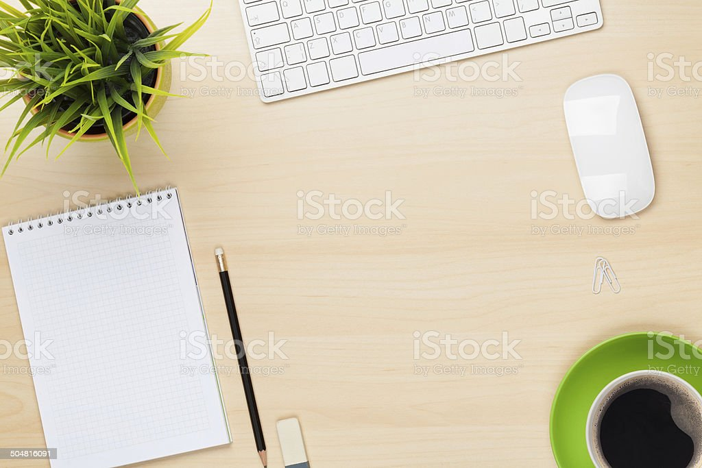 Office table with notepad, computer, flower and coffee cup stock photo