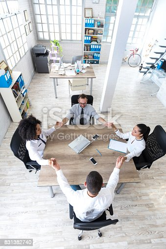 1016771914 istock photo Office team holding hands at work 831382740