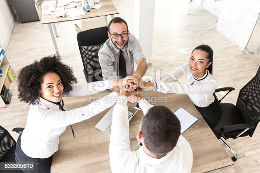 1016771914 istock photo Office team holding hands at work 833305610