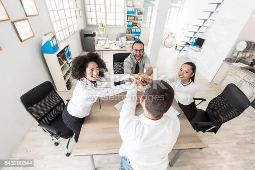 1016771914 istock photo Office team holding hands at work 843290344