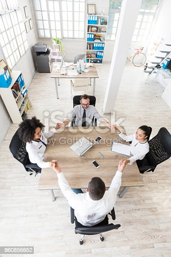 847516586 istock photo Office team holding hands at work 860856652