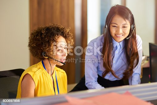 a young call centre representative greets a caller in a large open plan office as her supervisor watches over her shoulder and helps her through the call.