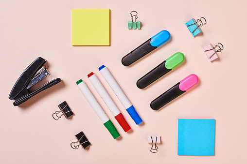 Highlighter pens, whiteboard markers, paper clips and sticker papers on pale pink background, flat lay shot