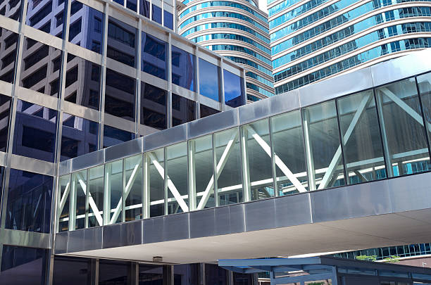 Office Towers Reflections and Skyway modern architecture of glass skyscrapers and reflections in windows with skyway over street elevated walkway stock pictures, royalty-free photos & images