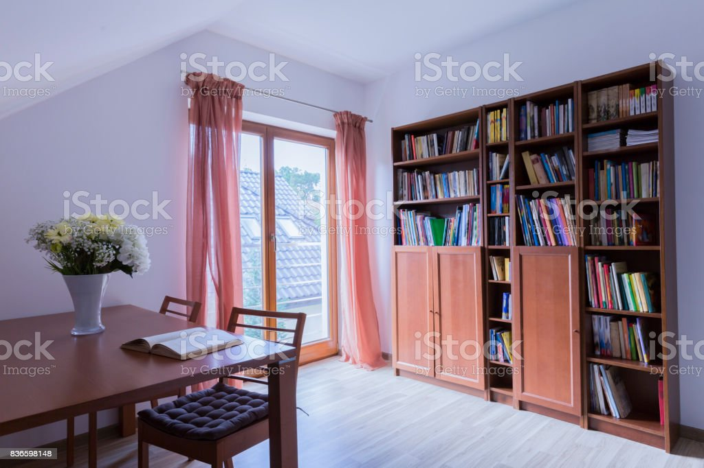 Office with wooden table and bookstand stock photo