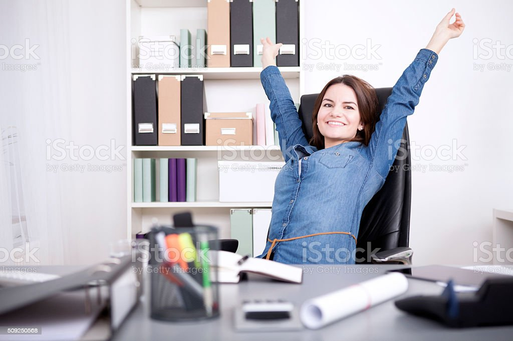 Office Woman Sitting on Chair Stretching her Arms stock photo