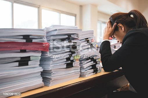 Office woman worker is distressed with a lot of paperwork on her desk