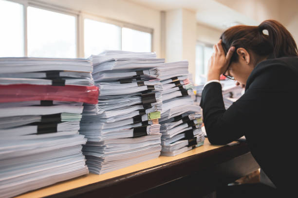 Office woman worker is distressed with a lot of paperwork on her desk. Office woman worker is distressed with a lot of paperwork on her desk overworked stock pictures, royalty-free photos & images