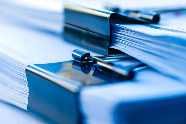 Office work concept - Paper with black clip stock photo
