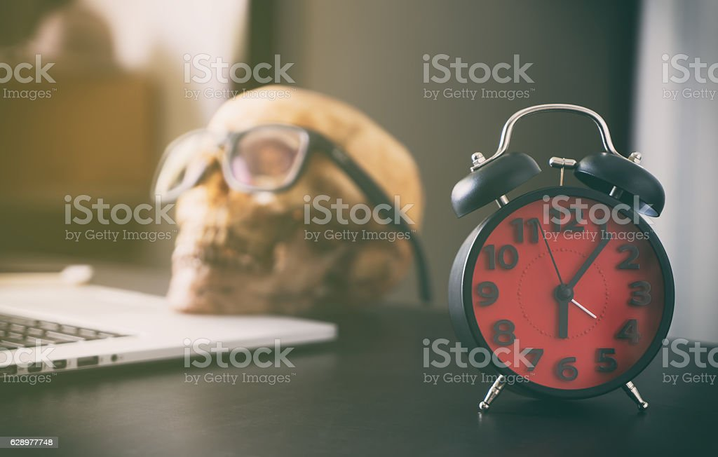 Office work Deadline with dead person skull. stock photo