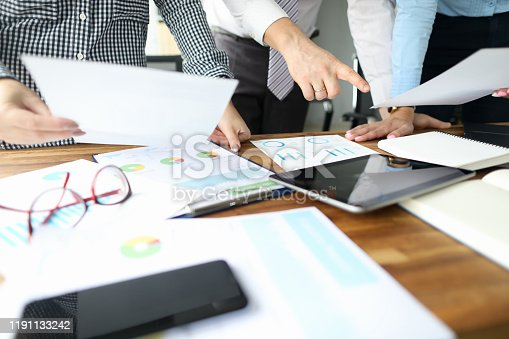 Close-up of people hands and important business paper lying on wooden table. Female hand holding sheet of paper. Man standing and pointing finger on tablet with empty screen