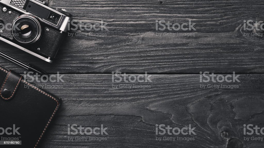 Office work space with camera, notebook, eyepieces, and pen. On a wooden surface. Top view. Free space for your text. stock photo