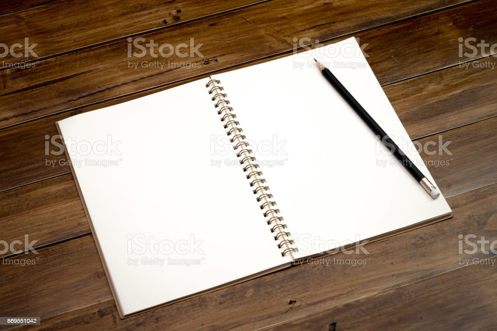 Office work table with notebook and pencil on brown wood desk table , Topview with workspace for add text or graphic stock photo