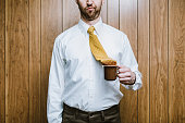 A business man in an office environment looks disappointed that his necktie has fallen in to his cup of coffee.  Workplace problems and humor.