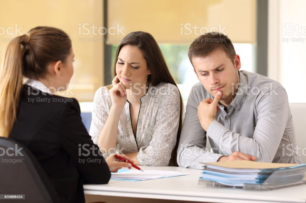 Office worker attending to a suspicious couple stock photo
