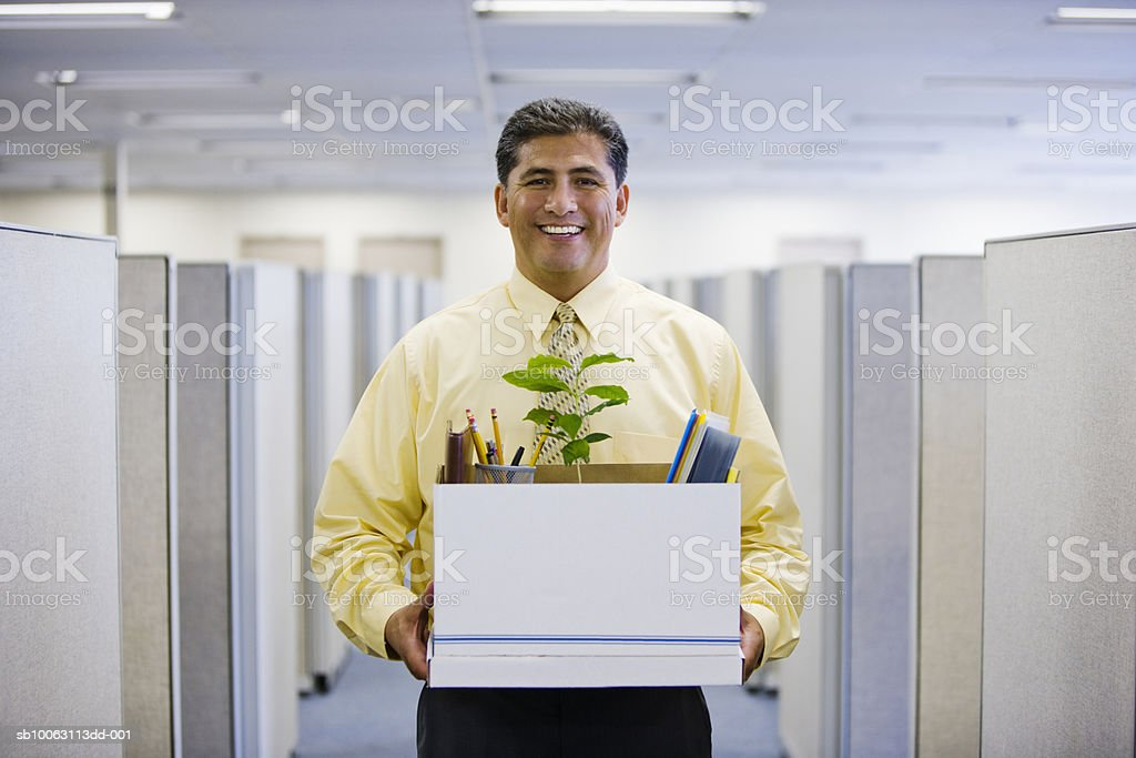 Office worker carrying box, smiling, portrait royalty-free stock photo