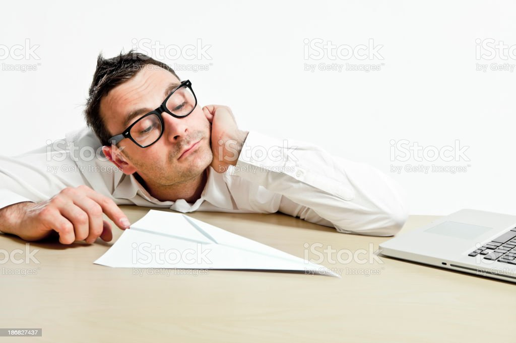 Office worker dreaming or boring, playing with paper airplane royalty-free stock photo