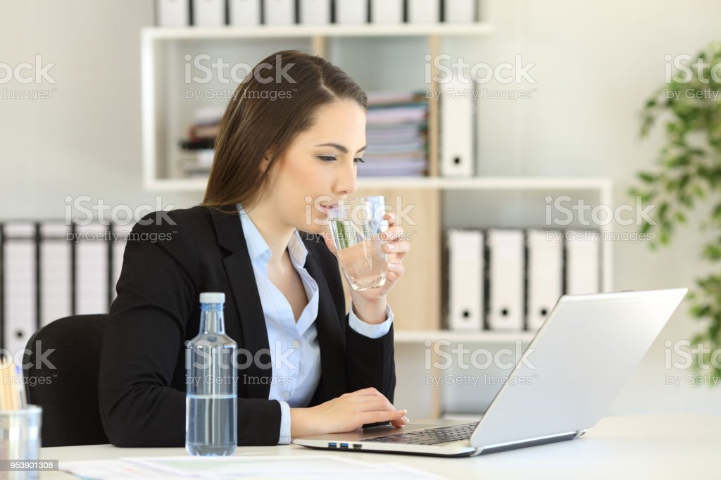 Office worker drinking water working on line stock photo