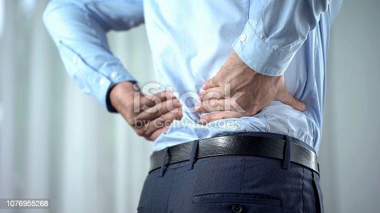 Office worker feeling sharp back pain, sedentary lifestyle, slipped disc