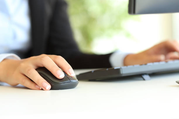 Office worker hand using computer mouse stock photo