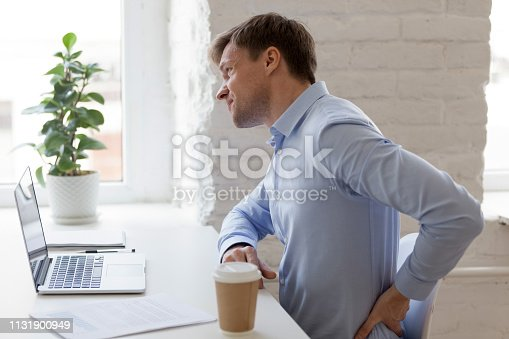 821012164istockphoto Office worker having strong lower back pain 1131900949