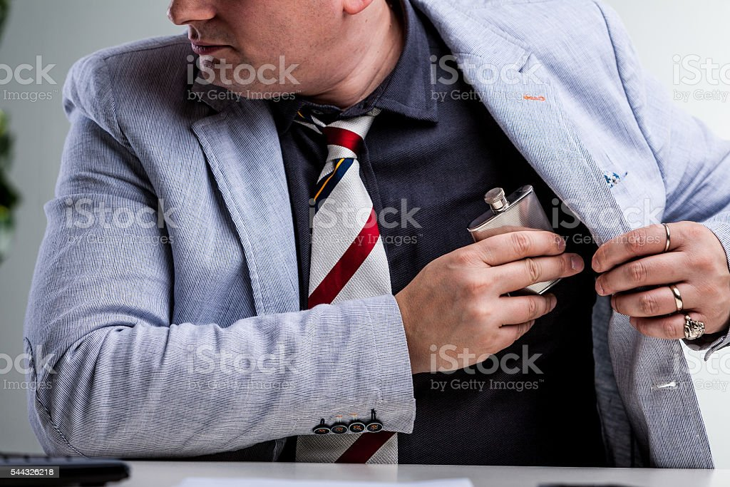 office worker hiding a flask in internal pocket stock photo