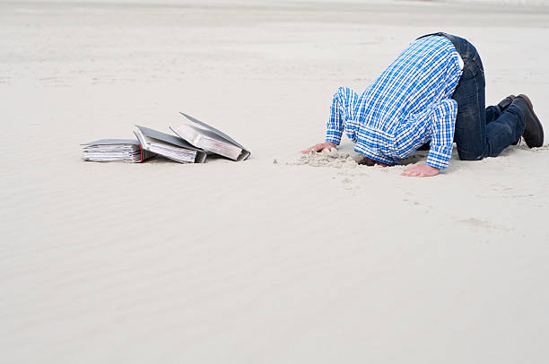 office worker hiding head in sand Office worker hiding head in sand because of excessive labor. Next to him some ring folders. head in the sand stock pictures, royalty-free photos & images