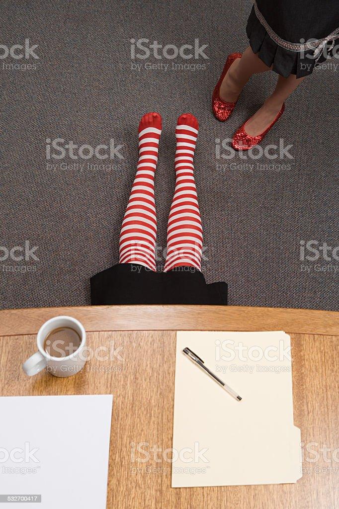 Office worker hiding under a desk stock photo