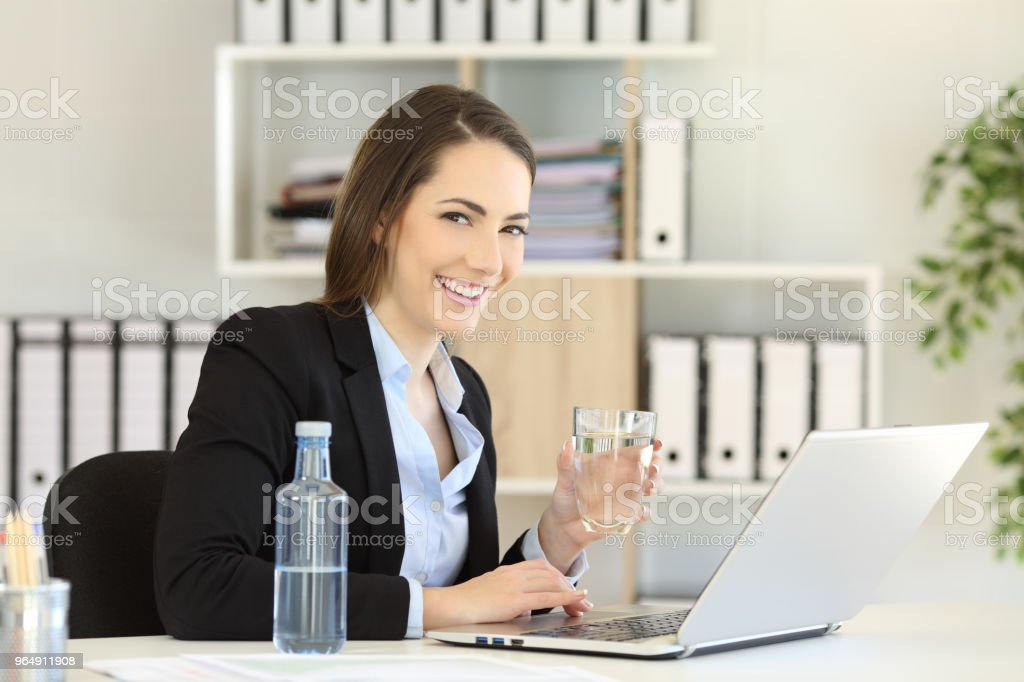 Office worker holding a water glass looking at camera royalty-free stock photo