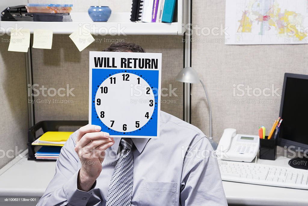 Office worker holding clock royalty free stockfoto
