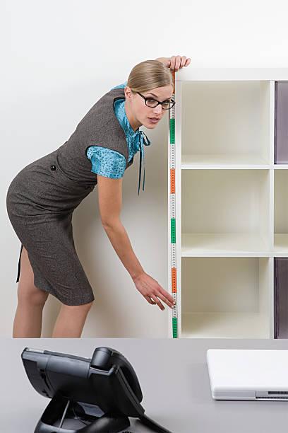 Office worker measuring shelves stock photo
