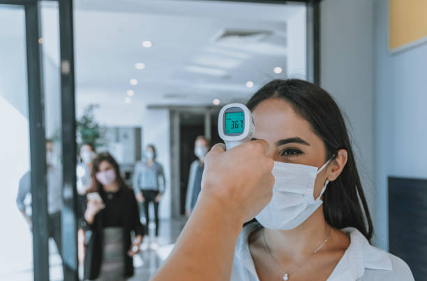 Office worker measuring temperature of business people with face mask for pandemic while coworkers go back to office stock photo