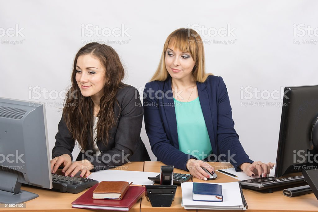 Office worker on the sly looks at monitor unsuspecting colleagues stock photo