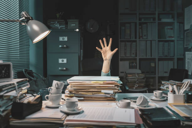 Office worker overwhelmed with paperwork stock photo