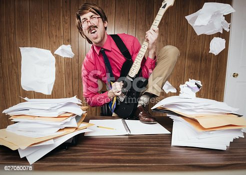 A white collar business man working in a retro 1980's style office stands on his desk piled with paperwork and documents, shredding some rock and roll on his electric guitar.  Papers are kick off of the desk from his antics.  GUITAR IS FULLY RELEASED.