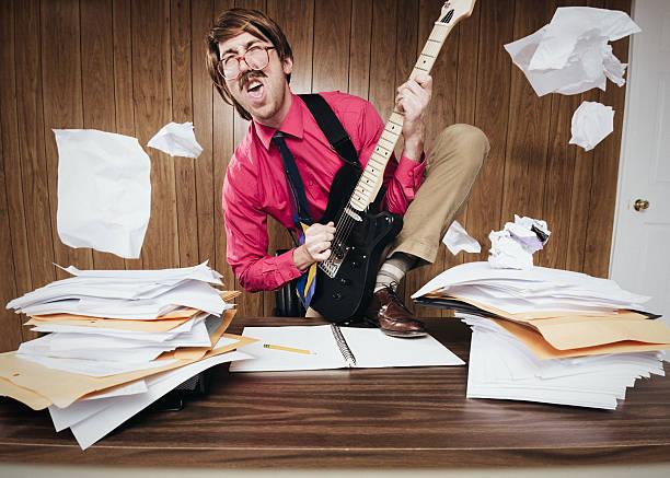office worker playing electric guitar - anti unordnung stock-fotos und bilder