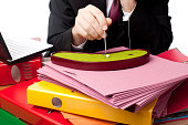 Office worker playing miniature golf on desk with folder stacks
