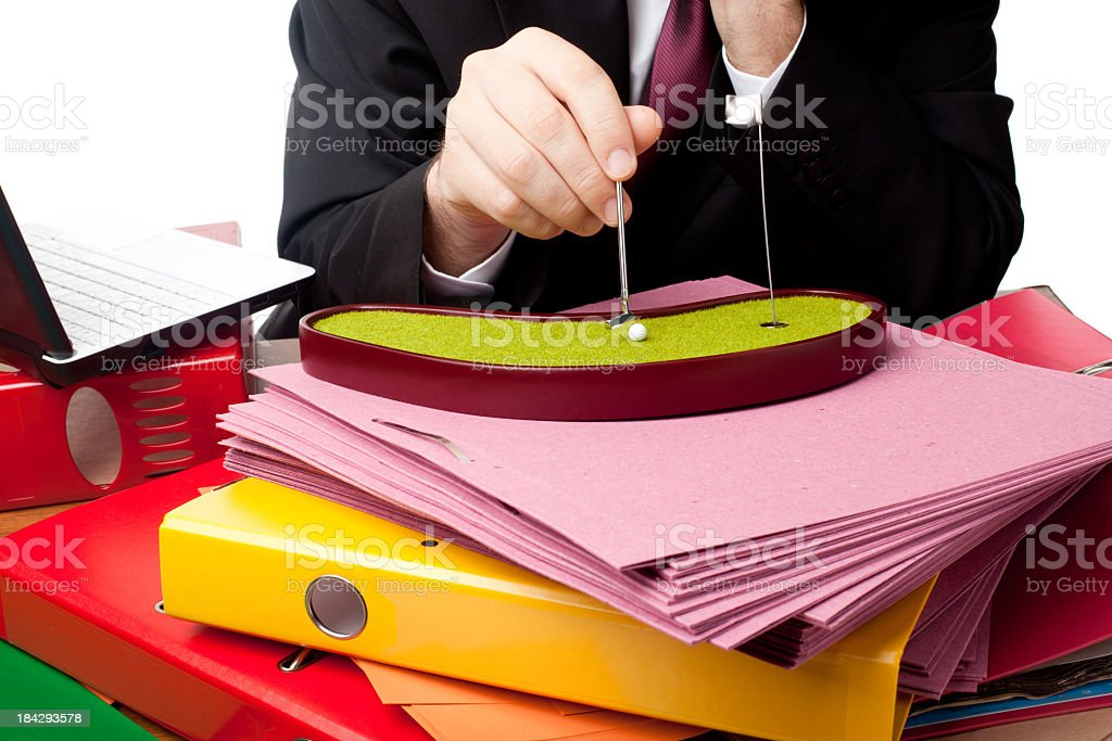 Office worker playing miniature golf on desk with folder stacks stock photo