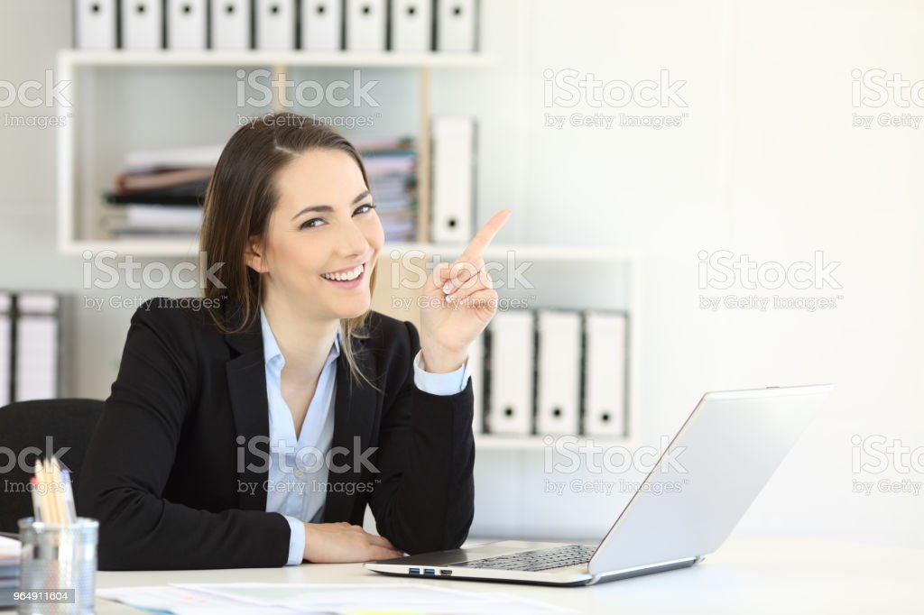 Office worker pointing at side and looking at camera royalty-free stock photo