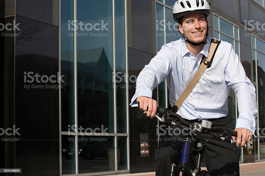 Office worker riding bicycle stock photo